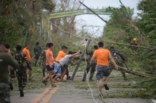 Rescue workers clear a road of debris and toppled electric posts caused by super Typhoon Mangkhut as they try to reach Baggao town