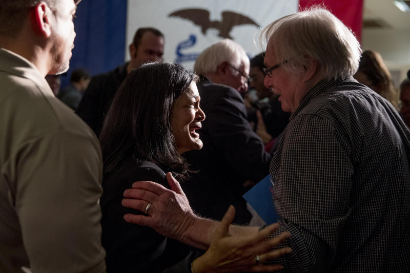 U.S. Rep. Pramila Jayapal, D-Wash, center left, and Democratic presidential candidate Sen. Bernie Sanders, I-Vt., background center, greet members of the audience at a campaign stop at the State Historical Museum of Iowa, Monday, Jan. 20, 2020, in Des Moines, Iowa. (AP Photo/Andrew Harnik)