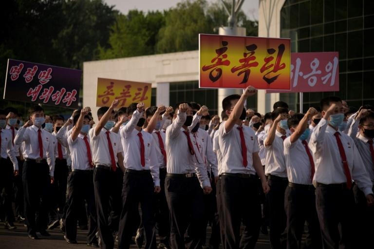 North Korean students take part in a rally denouncing 'defectors from the North' as they march in Pyongyang