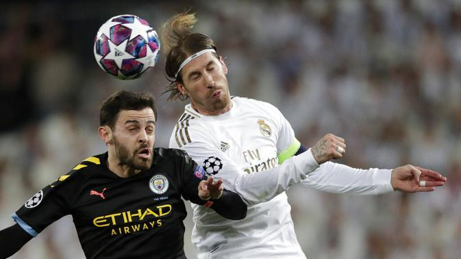 Gelandang Manchester City, Bernardo Silva, duel udara dengan bek Real Madrid, Sergio Ramos, pada laga liga Champions di Stadion Santiago Bernabeu, Rabu(26/2/2020). Manchester City menang dengan skor 2-1. (AP/Bernat Armangue)