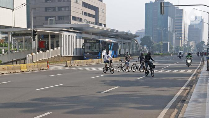 Warga berolahraga menggunakan sepeda di Bunderan HI Jakarta, Minggu (7/6/2020). Aturan itu tertuang dalam pasal 16 ayat 1 mengenai kegiatan sosial budaya. (Liputan6.com/Herman Zakharia)