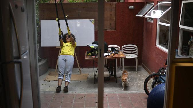 Atlet BMX asal Venezuela, Stefany Hernandez melakukan peregangan di rumahnya di Caracas, 25 April 2020. Di tengah karantina wilayah guna mengekang penyebaran Covid-19, peraih medali Olimpiade 2016 itu berlatih tiga kali seminggu untuk meraih tiket tampil di Olimpiade 2021. (AP/Matias Delacroix)