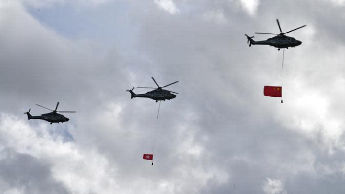 Bendera China (kanan) dan Hong Kong (tengah) diterbangkan dengan helikopter saat upacara untuk memperingati 23 tahun penyerahan Hong Kong dari Inggris ke China di Hong Kong, Rabu (1/7/2020). Hong Kong menandai 23 tahun penyerahan dari Inggris ke Cina pada 1 Juli. (Anthony WALLACE/AFP)