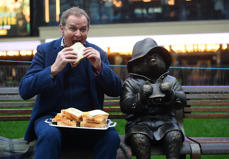 Hugh Bonneville eating a marmalade sandwich alongside a Paddington Bear statue as he attends the Scenes In The Square statue trail unveiling in Leicester Square, London. PA Photo. Picture date: Thursday February 27, 2020. Eight statues will be unveiled to mark a century's worth of cinema in the Square. Photo credit should read: Victoria Jones/PA Wire