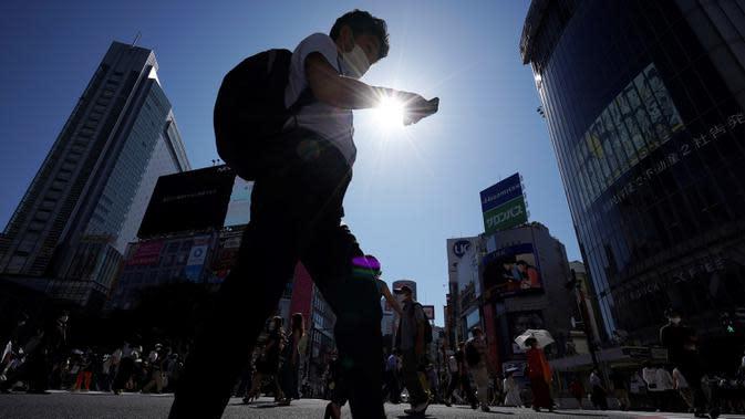 Pria yang memakai masker untuk mencegah penyebaran COVID-19 meyeberang jalan di Shibuya, Tokyo, Jepang, Jumat (3/7/2020). Jepang mengangkat darurat pandemi selama tujuh minggu pada akhir Mei, sebagian besar kegiatan sosial dan bisnis sejak itu telah kembali dimulai. (AP Photo/Eugene Hoshiko)