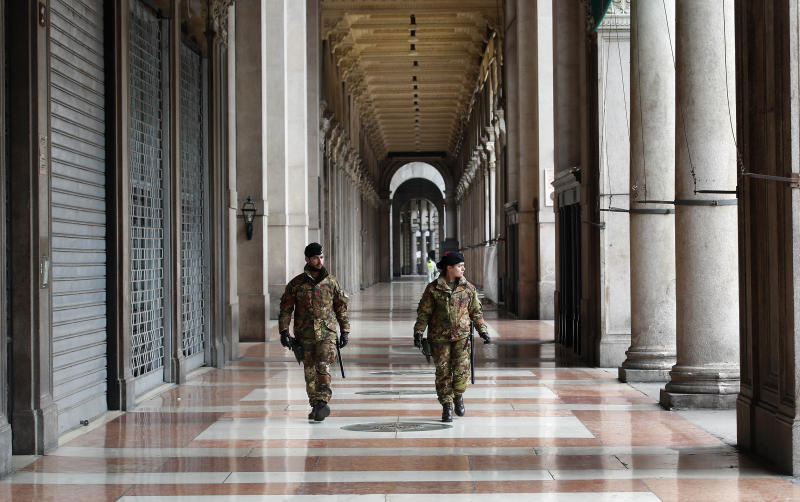 """Italian soldiers patrol downtown Milan, Italy, Sunday, March 22, 2020. Italian Premier Giuseppe Conte has told the nation he is tightening the lockdown to fight the rampaging spread of coronavirus, shuttind down all production facilities except those that are """"necessary, crucial, indispensible to guarantee"""" the good of the country.  For most people, the new coronavirus causes only mild or moderate symptoms. For some it can cause more severe illness, especially in older adults and people with existing health problems. (AP Photo/Antonio Calanni)"""