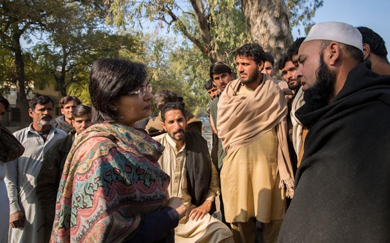 Dr Sania Nishtar, chair of the Benazir Income Support Programme, speaks to workers about their hardships as they gather outside a free communal kitchen for a meal - Saiyna Bashir