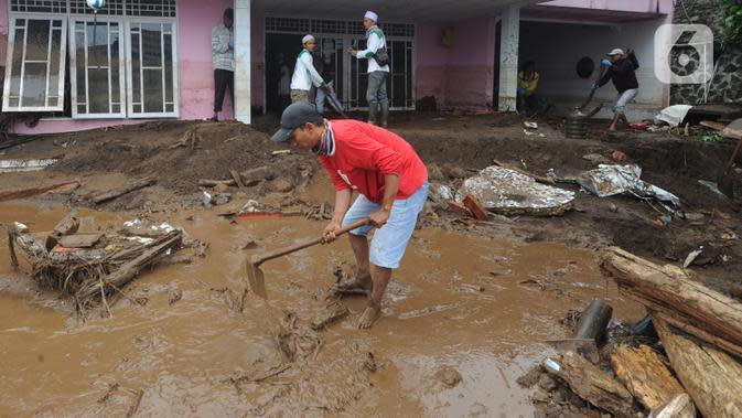 Warga membersihkan halaman rumah usai banjir bandang melanda Kampung Cibuntu, Desa Pasawahan, Kecamatan Cicurug, Sukabumi, Jawa Barat, Selasa (22/9/2020). Data sementara puluhan bangunan rusak berat, 12 rumah hanyut, dan dua korban hilang masih dicari. (merdeka.com/Arie Basuki)