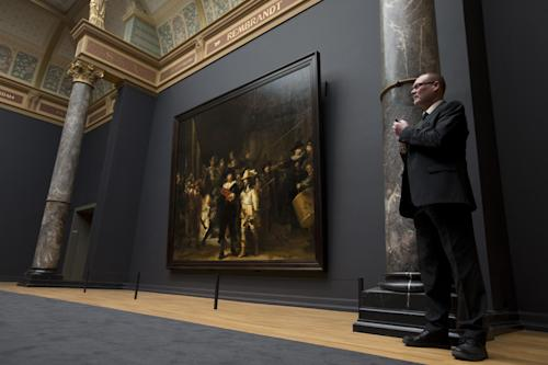 A senior security officer stands next to Dutch master Rembrandt's The Night Watch painting during a press preview of the renovated Rijkmuseum in Amsterdam, Thursday, April 4, 2013. The Rijksmusuem, home of Rembrandt's Night Watch and other national treasures, is preparing to reopen its doors on April 13, 2013 after a decade-long renovation. (AP Photo/Peter Dejong)