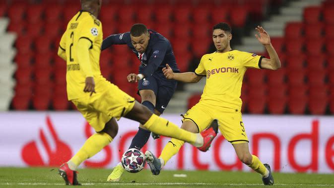 Penyerang PSG, Kylian Mbappe (tengah) menendang bola dari kawalan dua pemain PSG, Achraf Hakimi dan Dan-Axel Zagadou pada pertandingan leg kedua babak 16 besar Liga Champions di stadion Parc des Princes, Paris, Prancis (12/3/2020). PSG menang 2-0 atas Dortmund. (UEFA via AP)