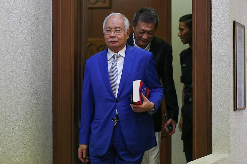 Datuk Seri Najib Razak seen here with the book 'The Laws of Human Nature' at the Kuala Lumpur court complex June 13, 2019. — Picture by Yusof Mat Isa