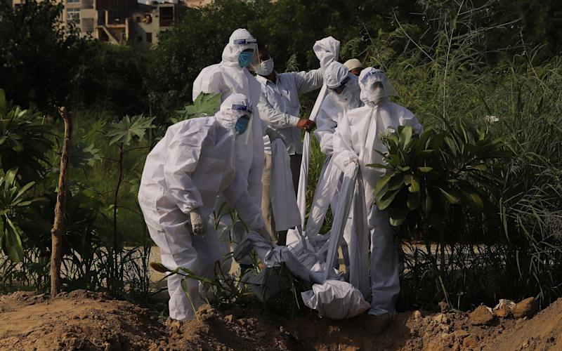 Relatives lower the body of a person who died from the novel coronavirus pandemic at a graveyard in New Delhi - Anadolu
