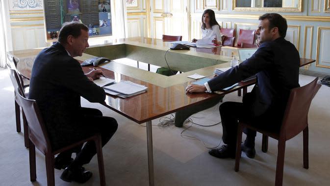 Presiden Prancis Emmanuel Macron (kanan) saat mengikuti KTT Luar Biasa G20 secara virtual dari Istana Elysee di Paris, Prancis, Kamis (26/3/2020). Para pemimpin dunia mengkoordinasikan respons global terhadap pandemi virus corona COVID-19. (Benoit Tessier/Pool via AP)