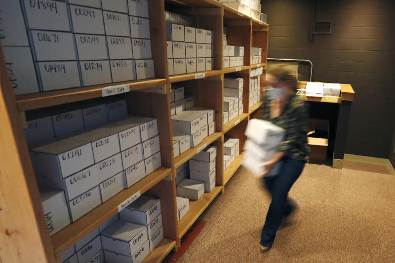 In this Tuesday, May 5, 2020, photo, Cook County Medical Examiner's Indigent Coordinator, Rebeca Perrone, begins placing 24 boxes of unclaimed cremated remains on a shelf, adding to over 500 other boxes at the county morgue in Chicago. Numbers of unclaimed remains are up, Perrone says. Lost wages amid business shutdowns mean some families can't afford the minimal $250 fee to collect the boxes. (AP Photo/Charles Rex Arbogast)