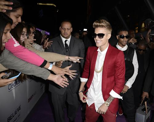 """Singer Justin Bieber arrives at the premiere of the feature film """"Justin Bieber's Believe"""" at Regal Cinemas L.A. Live on Wednesday, Dec. 18, 2013, in Los Angeles. (Photo by Dan Steinberg/Invision/AP)"""