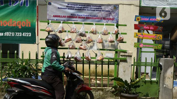 Pengemudi ojek online mengambil sembako yang digantung di rak kayu di kawasan Rawa Barat, Jakarta Selatan, Kamis (14/5/2020). Selama masa pandemi COVID-19, pihak kelurahan dan masjid sekitar menyediakan paket berisi mi instan, telur, dan masker untuk warga yang membutuhan. (merdeka.com/Imam Buhori)