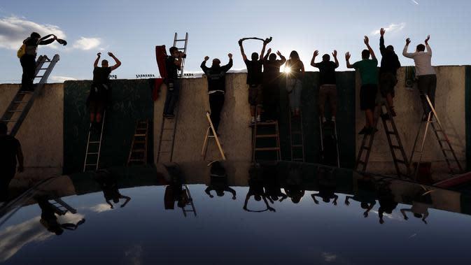 Penggemar, berdiri di tangga dari belakang pagar, merayakan gol saat mereka menonton pertandingan divisi pertama Ceko antara Bohemians Prague dan Zlin di Praha (4/10/2020). Para penggemar mencari cara inovatif untuk menonton pertandingan selama pandemi virus corona. (AP Photo/Petr David Josek)