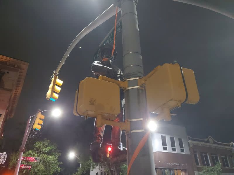 A Confederate statue is seen hanging on a street post in Raleigh