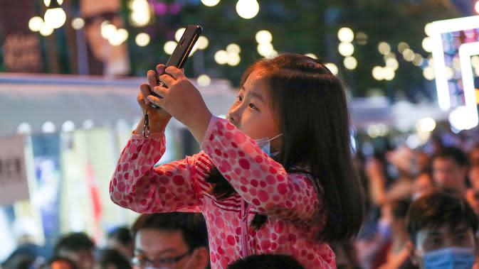 Seorang anak mengambil foto di sebuah pasar malam di Shanghai, China timur (6/6/2020). Sejumlah bar, museum, toko buku, pusat perbelanjaan, dan kompleks komersial besar ikut serta dalam festival itu dengan jam operasional yang diperpanjang. (Xinhua/Ding Ting)
