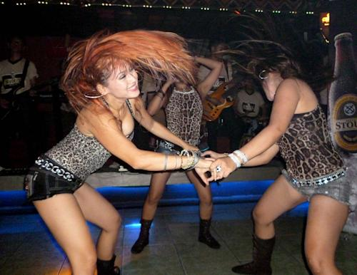 In this photo taken Friday, May 25, 2012, singers perform during a dangdut show at a pub in Jakarta, Indonesia. As U.S. pop star Lady Gaga canceled her sold out concert in Jakarta over security concerns after Muslim hardliners threatened to use violence against her, many started to question the extremists' double standard towards the raunchy dangdut shows performed almost every night by young Indonesian women who turn up everywhere from smokey bars and ritzy nightclubs to weddings and even circumcisions. Dangdut is the most popular music among lower class people in Indonesia. (AP Photo/Robin McDowell)
