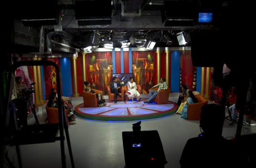 """In this July 26, 2013 photo, Nidhi Gaur, left on stage, and her fiance Rahul Rai, right on stage, participate in """"So It's Final,"""" a talk show on Shagun TV that features engaged couples in Noida, India. Indians are obsessed with weddings and obsessed with reality television. Now Shagun TV, a new television channel headquartered in a sprawling suburb of India's capital, is hoping it has found a can't-miss idea — merging the two into a 24-hour matrimonial TV station.(AP Photo/Tsering Topgyal)"""