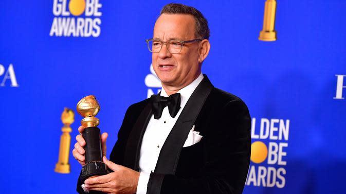 Aktor Tom Hanks berpose di ruang pers dengan penghargaan Cecil B. Demille selama Golden Globe Awards ke-77 di Beverly Hills, California pada 5 Januari 2020. Hanks (63) mengatakan dia dan Wilson menderita demam saat berada di Australia, dan sekarang akan diisolasi dan diawasi. (AFP/Frederic J. Brown)