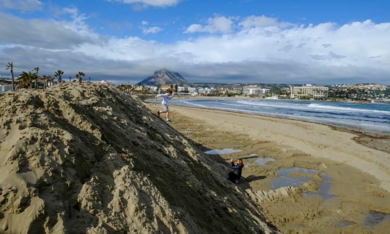 """People walk past a huge sand shaft built to protect the Arenal Beach ahead of the upcoming storm """"Gloria"""", in Javea near Alicante"""