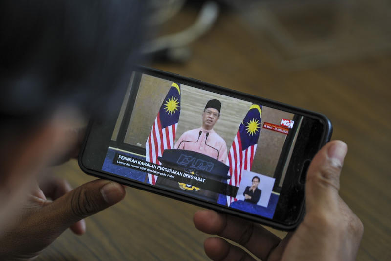 A man watches the live telecast of Prime Minister Tan Sri Muhyiddin Yassin's special address about the conditional movement control order in Kuala Lumpur May 10, 2020. — Picture Shafwan Zaidon