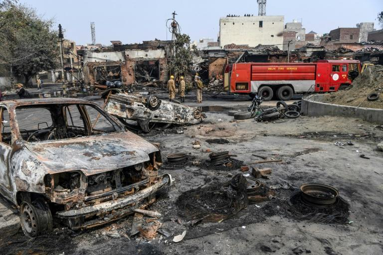 Firefighters douse burnt-out tyre market premises on February 26 following clashes in New Delhi