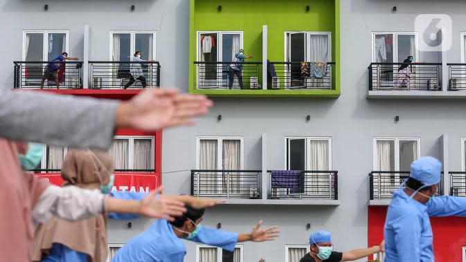 Pasien orang tanpa gejala (OTG) Covid-19 mengikuti senam pagi bersama tenaga medis dari atas balkon di Rumah Singgah Karantina Covid-19 Kabupaten Tangerang, Selasa (26/5/2020). Senam pagi yang diikuti 40 OTG berlangsung sekitar 30 menit mulai pukul 08.00 WIB. (Liputan6.com/Fery Pradolo)