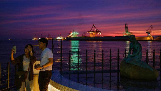 Pasangan yang sedang berpose untuk berfoto di kawasan pejalan kaki pelabuhan di Osaka (20/9/2020). Pelabuhan Osaka adalah salah satu pelabuhan utama di Jepang, berlokasi di Teluk Osaka. (AFP/Philip Fong)