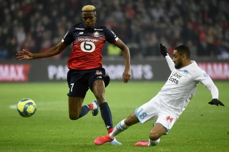 Victor Osimhen (L) of Lille is tackled by Jordan Amavi of Marseille