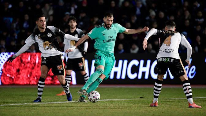 Striker Real Madrid, Karim Benzema berebut bola dengan bek Unionistas de Salamanca, Inigo Zubiri pada pertandingan babak ke-32 besar Copa del Rey 2019-2020 di Pistas del Helmantico, Rabu (22/1/2020). Madrid harus berjuang keras untuk menang 3-1 atas tim divisi tiga, Unionistas. (JAVIER SORIANO/AFP)