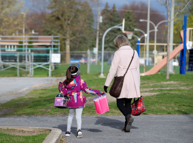 A student is escorted into the schoolyard by a teacher as schools reopen outside the greater Montreal region in Saint-Jean-sur-Richelieu