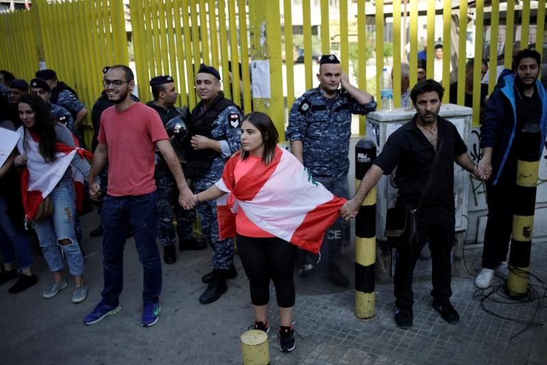 Demonstrators stand blocking access to the state owned electricity company during ongoing anti-government protests in Beirut