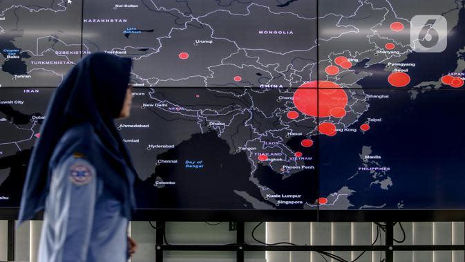 Petugas melewati layar pemantau yang menunjukan penyebaran virus corona (COVID-19) di Dinas Kesehatan DKI Jakarta, Senin (9/3/2020). Dari 3.580 orang yang menghubungi Posko COVID-19 DKI Jakarta, ada 64 kasus kategori Orang Dalam Pantauan dan 56 Pasien Dalam Pengawasan. (Liputan6.com/Faizal Fanani)