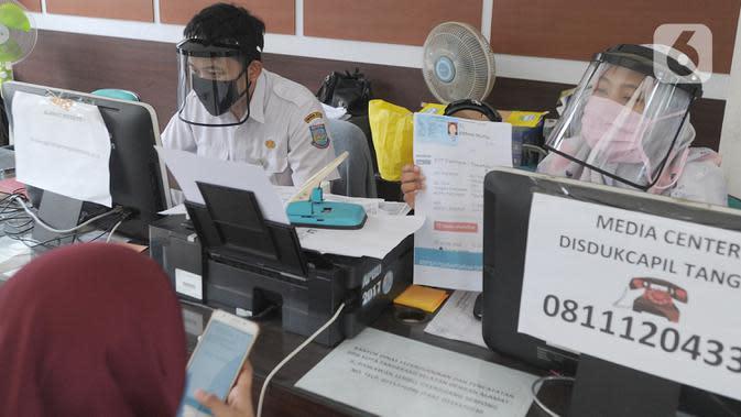 Petugas Dinas Kependudukan dan Catatan Sipil menggunakan pelindung wajah saat melayani warga di Kecamatan Pamulang, Tangerang Selatan, Rabu (3/6/2020). Sejumlah kantor pelayanan pemerintah melaksanakan protokol kesehatan yang ketat untuk memutus rantai penyebaran covid-19. (merdeka.com/Arie Basuki)
