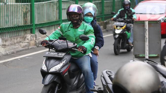 Pengemudi ojek online mengangkut penumpang di Shelter Sudirman, Jakarta, Senin (8/6/2020). Pemprov DKI mulai mengizinkan ojek daring maupun konvensional mengangkut penumpang di PSBB transisi dengan menerapkan protokol kesehatan. (Liputan6.com/Angga Yuniar)