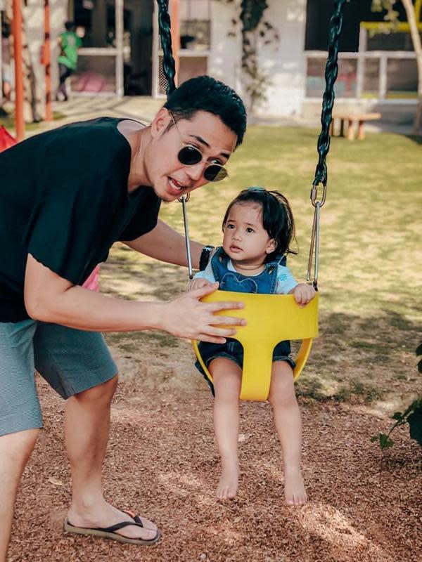 Meski hanya menemani sang putri bermain ayunan, nyatanya Kinos juga tampil simpel sekaligus trendi. Ia mengenakan kaus dan celana pendek tapi juga memakai kacamata hitam. Lembar tampak antusias saat berada di ayunan tersebut dengan menatap sang ayah terus menerus. (Liputan6.com/IG/@kinosnoski)