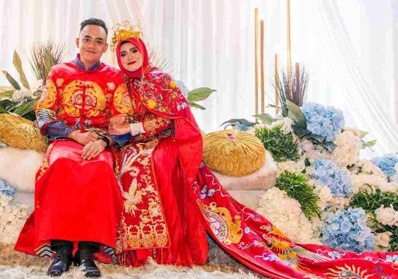 Ag Mohd Syafiq and wife, May Phang, both in traditional Chinese attire.