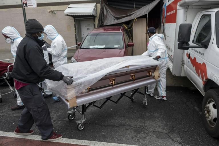 People wearing hazmat suits and masks transport a casket into a funeral home in Brooklyn on April 30, 2020 where dozens of decomposing bodies were found in trucks