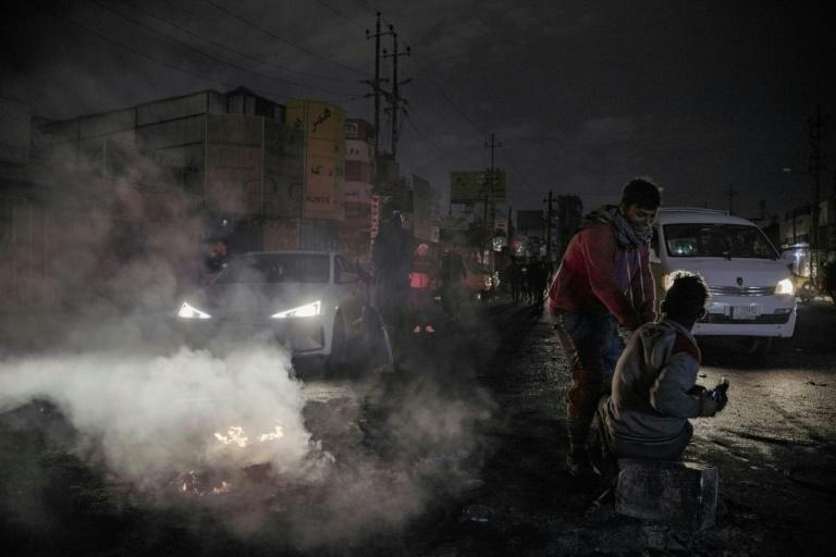 Iraqi youths block a street leading to Baghdad's al-Tayaran square on January 21