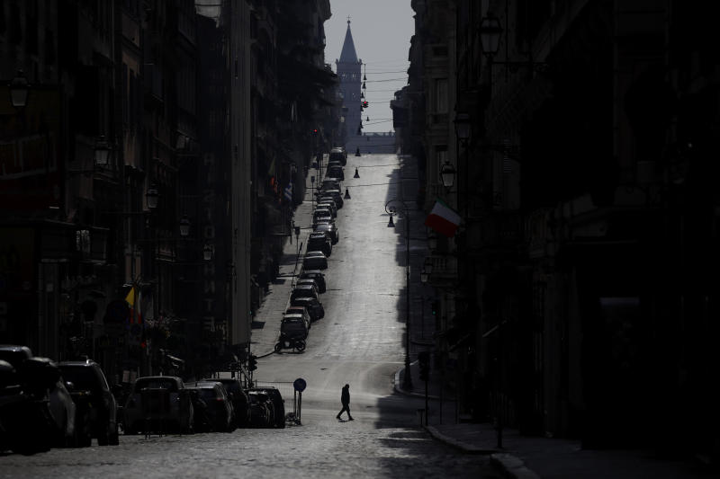 """A man walks along a road leading to St. Mary Major Basilica, silhouetted in background, in Rome, Sunday, March 22, 2020. Italian Premier Giuseppe Conte has told the nation he is tightening the lockdown to fight the rampaging spread of coronavirus, shuttind down all production facilities except those that are """"necessary, crucial, indispensible to guarantee"""" the good of the country. For most people, the new coronavirus causes only mild or moderate symptoms. For some it can cause more severe illness, especially in older adults and people with existing health problems. (AP Photo/Alessandra Tarantino)"""