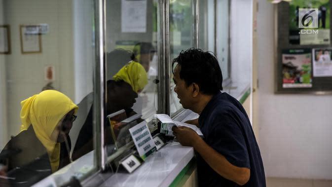 Warga saat bertransaksi di pegadaian di Jakarta, Kamis (15/6). Meningkatnya kebutuhan masyarakat jelang Lebaran membuat banyak orang menggadaikan barang berharga guna memenuhi kebutuhan yang mendesak. (Liputan6.com/Faizal Fanani)