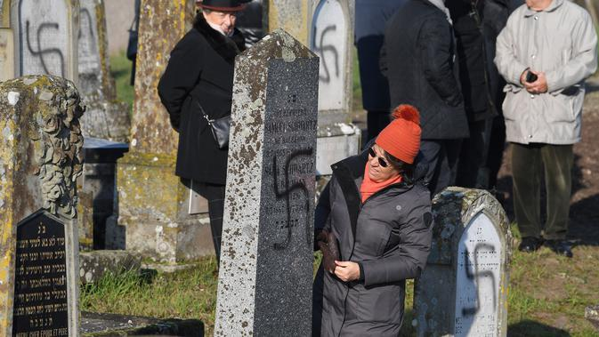 Seorang wanita melihat kondisi salah satu nisan yang dicoreti lambang swastika Nazi di pemakaman Yahudi, Westhoffen, dekat Strasbourg, Prancis, Rabu (4/12). Sedikitnya 107 makam menjadi sasaran vandalisme dengan dicoreti lambang swastika Nazi. (AFP/Patrick Hertzog)