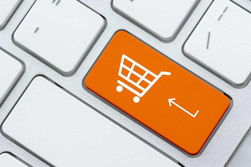 Online shopping / ecommerce and retail sale concept : White basket for checkout, shopping cart symbol on a laptop keyboard, depicts customers order / buy things from retailer sites using the internet
