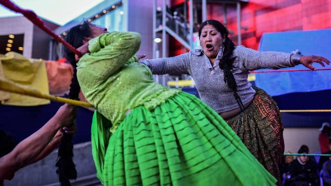 Pegulat Bolivia Ana Luisa Yujra (kiri), bertarung dengan lawannya, Lidia Flores, di atas ring gulat di El Alto, pada 24 November 2019. Di Bolivia ada sebuah atraksi gulat yang diperankan perempuan dengan menggunakan busana khas warga Bolivia. (Ronaldo SCHEMIDT / AFP)