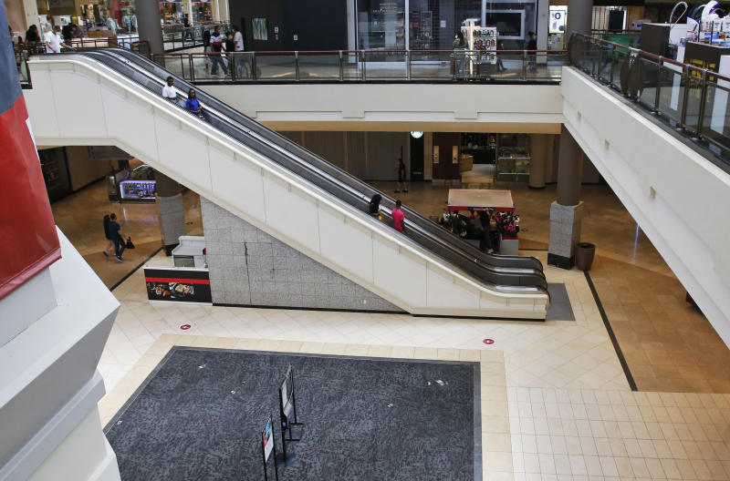 FILE - In this May 1, 2020, file photo, people ride down an escalator at a shopping mall in Oklahoma City as it reopens from its closure since mid-March due to coronavirus concerns. Many businesses are requiring customers and workers to sign forms saying they won't sue if they catch COVID-19. Businesses are afraid they could face lawsuits even if they follow social distancing and other government guidelines as they reopen across the U.S. after coronavirus shutdowns. (AP Photo/Sue Ogrocki, File)