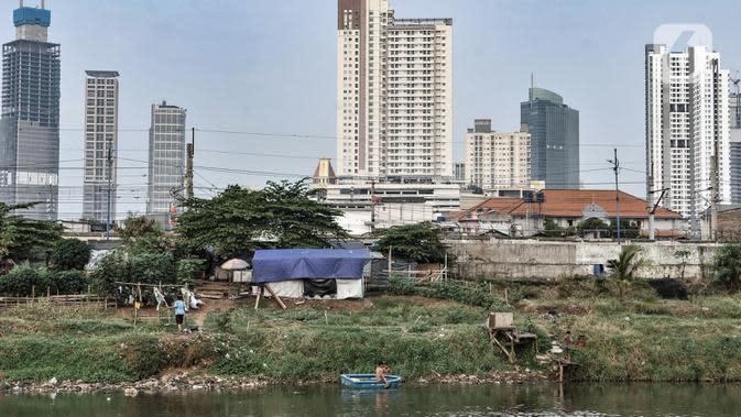 Aktivitas warga di bantaran Kanal Banjir Barat dengan latar belakang gedung pencakar langit di Jakarta, Kamis (6/8/2020). Badan Pusat Statistik mencatat pertumbuhan ekonomi Indonesia Kuartal II/2020 minus 5,32 persen akibat perlambatan sejak adanya pandemi COVID-19. (merdeka.com/Iqbal S. Nugroho)