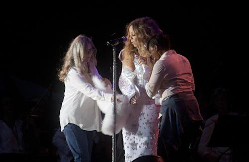 Mariah Carey has people help her with sling as she performs in Central Park during the All-Star Charity Concert to benefit Hurricane Sandy victims on Saturday, July 13, 2013 in New York. (Photo by Carlo Allegri/Invision/AP Images)